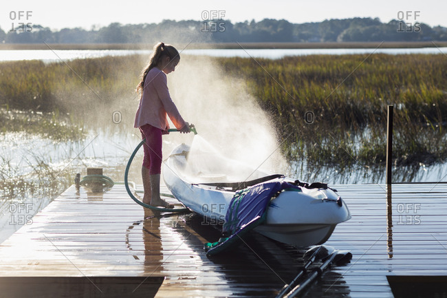 Girl spraying canoe on wooden dock over lake