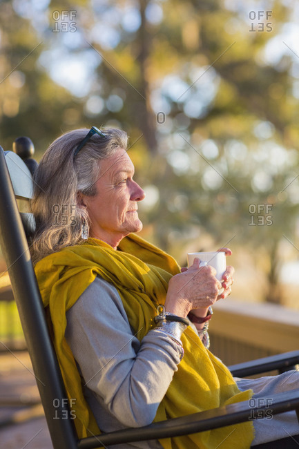 Older Woman drinking coffee in rocking chair