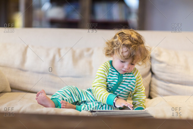 Baby boy using digital tablet on sofa