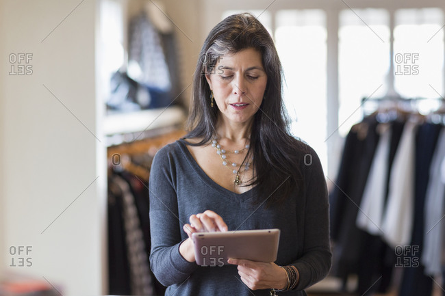 Small business owner using digital tablet in store