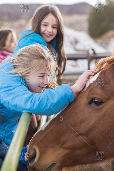 Girls petting horse on ranch