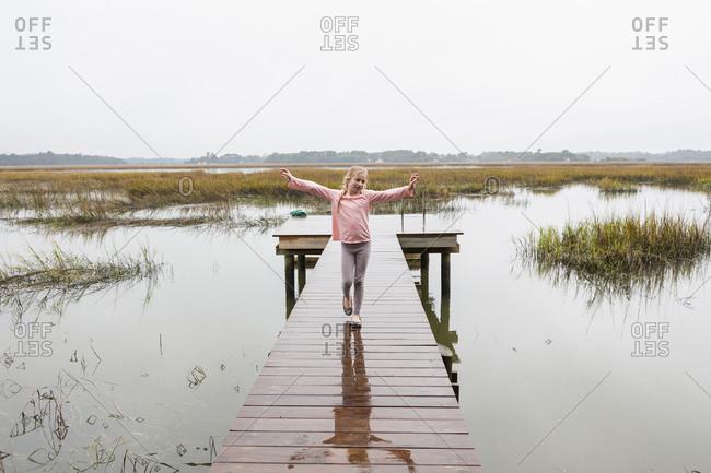 Girl standing on wooden dock over lake