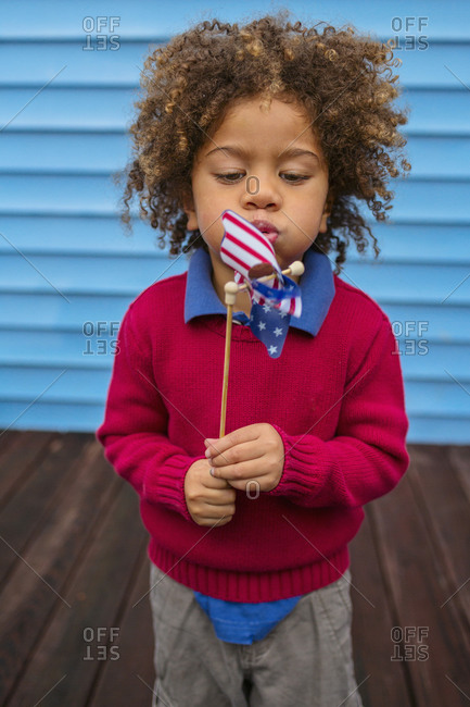 Boy blowing patriotic pinwheel