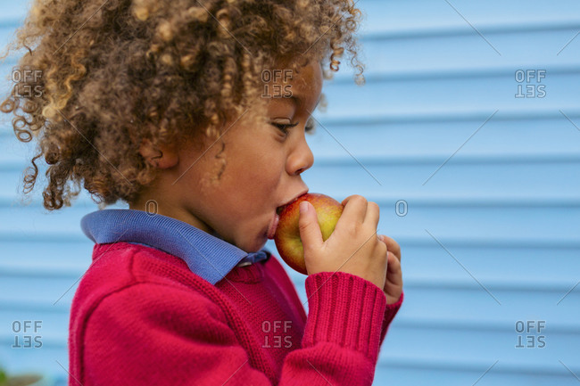 Boy eating apple outdoors