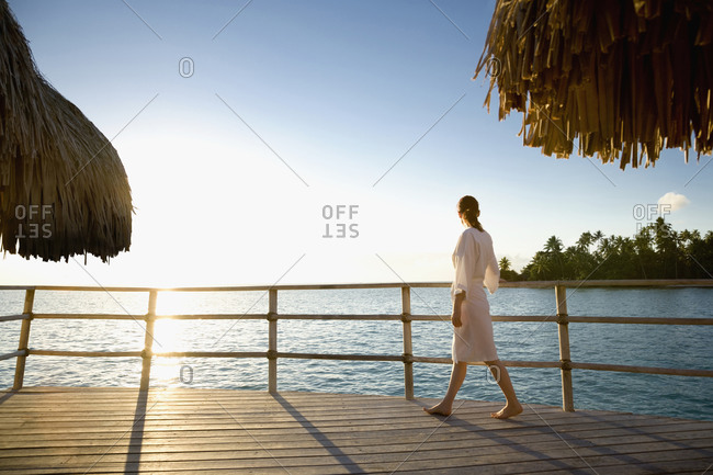 Woman admiring ocean from wooden deck