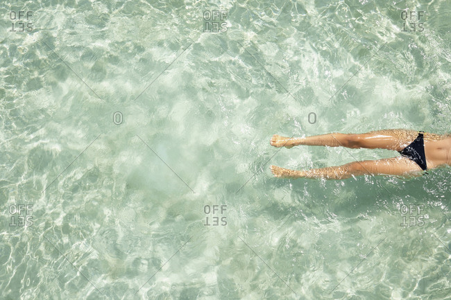 Overhead view of Woman floating in tropical ocean