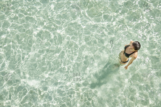 Overhead view of Woman standing in tropical ocean