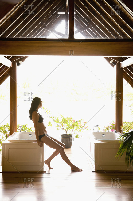 Woman sitting on bathtub in spa