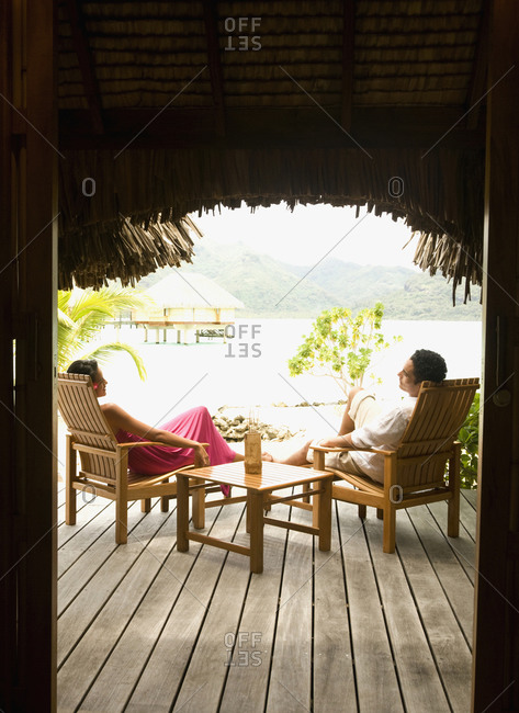Couple relaxing in lawn chairs on wooden deck