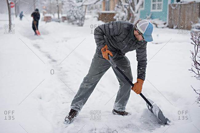 A man shoveling sidewalk