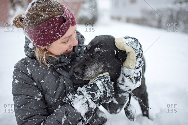 Woman hugging dog in the snow