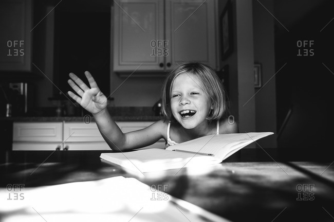 Girl laughing doing her homework