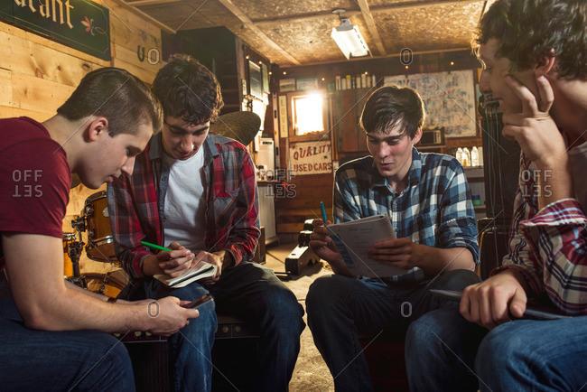 Teen boys writing songs in garage