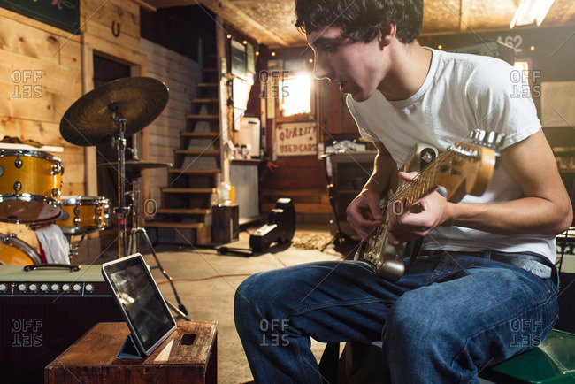Teen with guitar looking at tablet