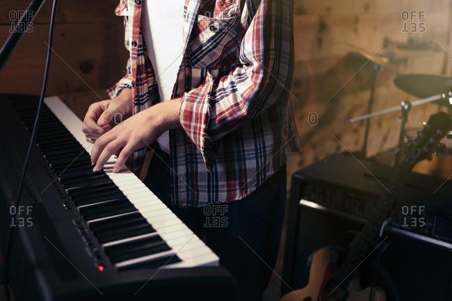 Teen playing a keyboard