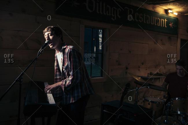 Teen at keyboard playing and singing