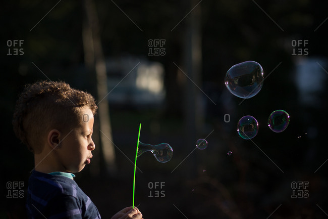 Boy watches bubbles form while blowing into a bubble wand