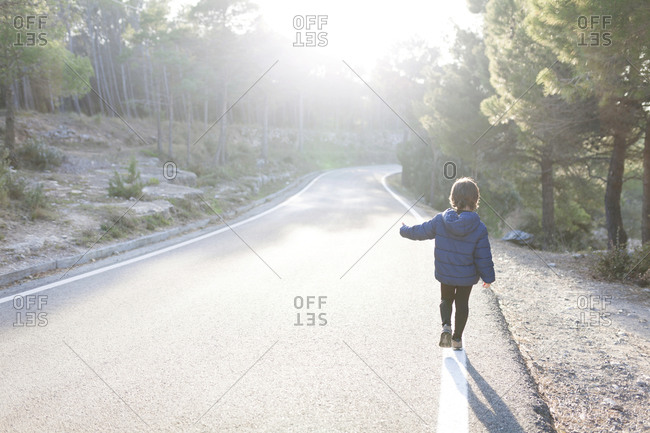 Back view of little boy walking on side line of empty country road