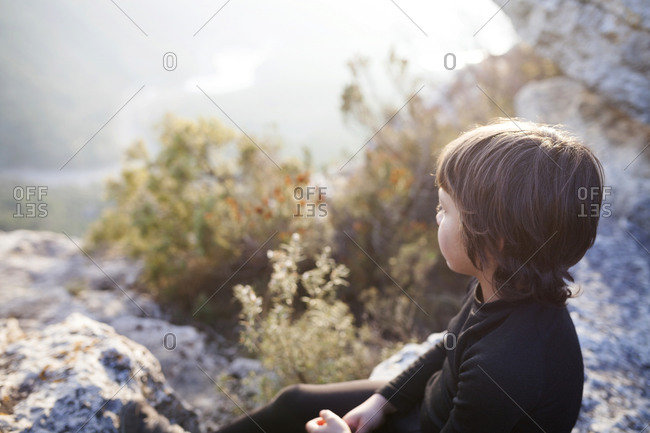 Little boy relaxing on a rock