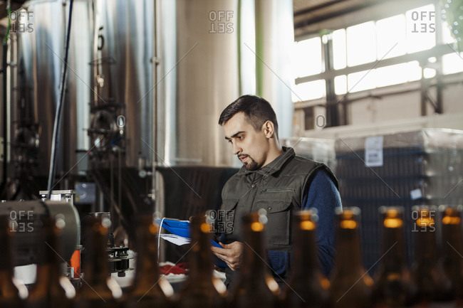 Young man working in craft brewery