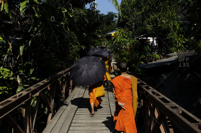 Monks walking in a row along a small foot bridge