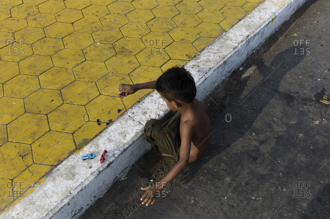 Shirtless boy playing with toy cars on a curb at the edge of the street