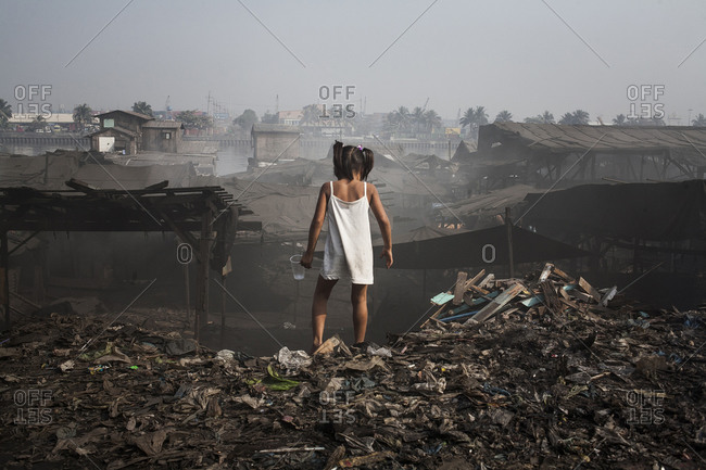 Girl standing on the edge of a trash mound in a slum in the Philippines
