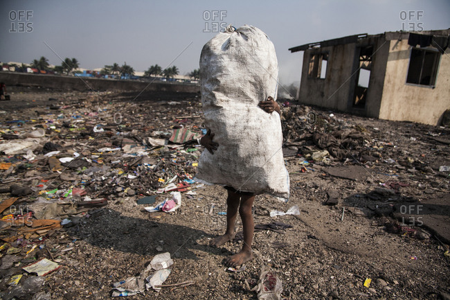 Child standing in a vacant trash strewn lot holding a white burlap sack