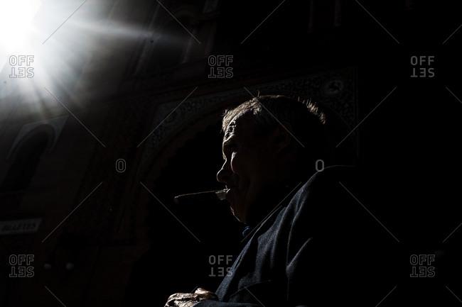 Man smoking a cigar partially lit by a bright light
