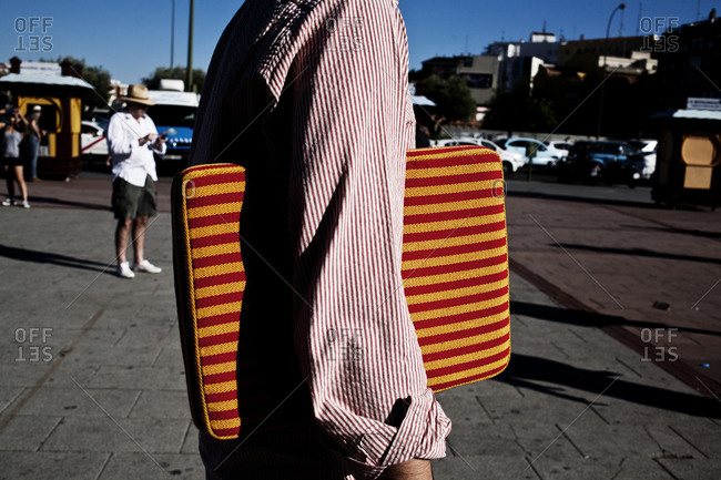 Person wearing a striped shirt carrying a striped cushion