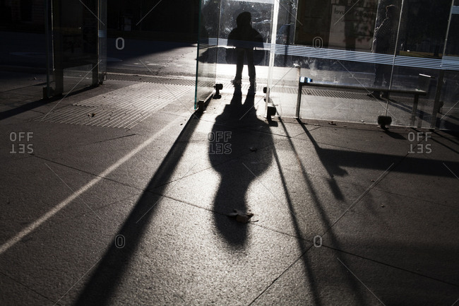 Shadow of a person sitting at a bus stop