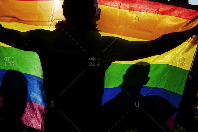Silhouetted figures holding the rainbow LGBT pride flag