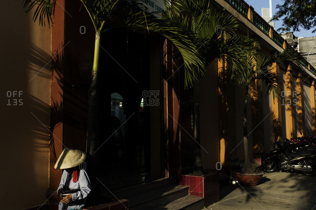 Person walking along sidewalk under palm trees wearing an Asian conical hat