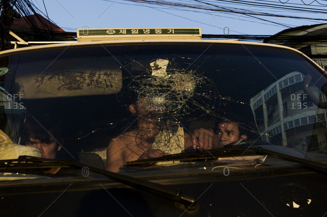 Three men sitting in a taxi with a broken windshield
