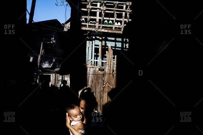 Woman holding a baby in the shadow of a rundown wooden building