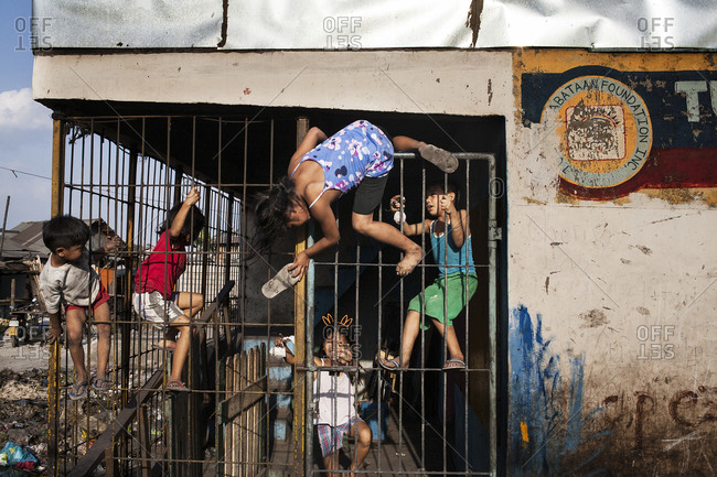 Children playing together on a building with iron bars over the doorway
