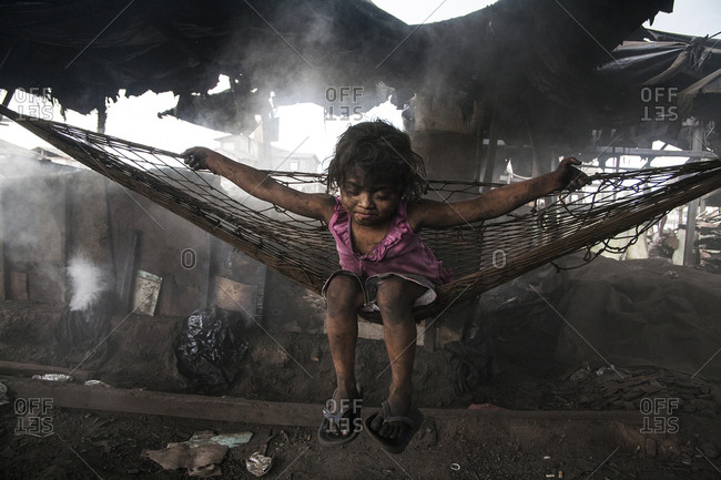 Girl sitting on a hammock in a smoldering trash strewn shelter in a slum in the Philippines