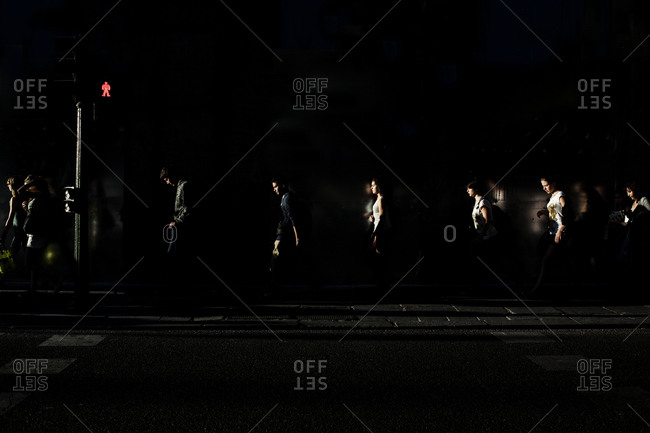Line of people walking in the shadows along the street past a street light