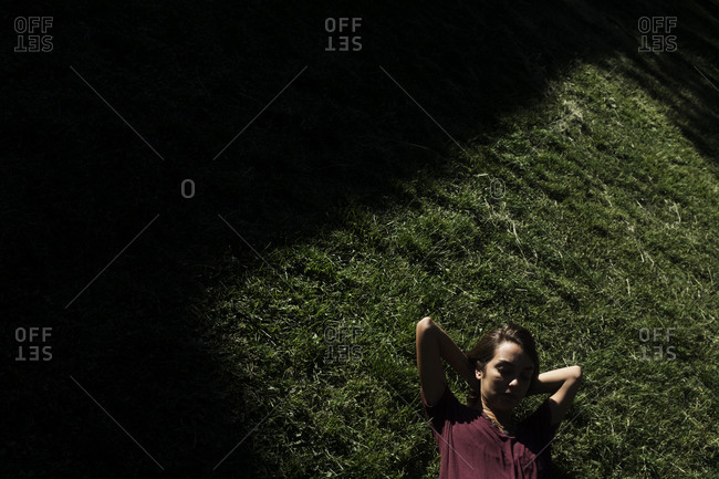 Woman lying in the grass with her hands behind her head
