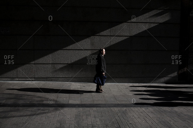 Man walking in shadows along a city sidewalk