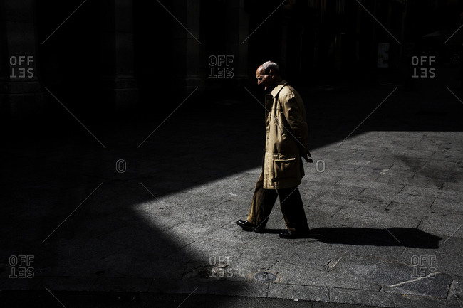 Middle aged man walking alone on a sidewalk in the city of Madrid, Spain