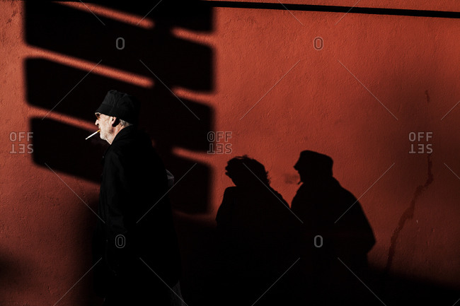 Couple walking by a wall trailing shadows