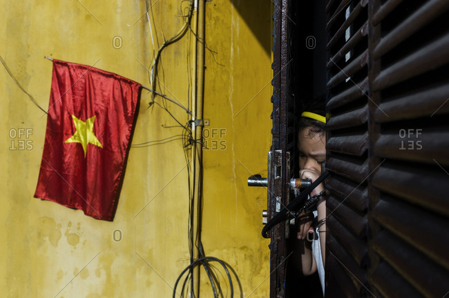 Young girl peaking through a heavily chained door next to a yellow wall emblazoned with the flag of Vietnam