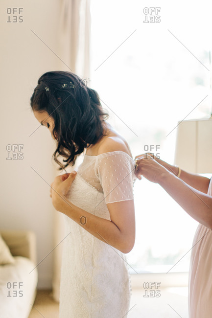 Woman helping bride button her gown before wedding