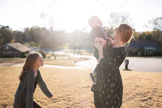 Woman lifting toddler son as young daughter watches