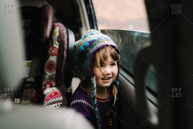 Little girl with a knit hat inside a van