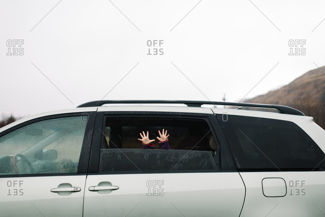 Young child's hands sticking out frosted van window