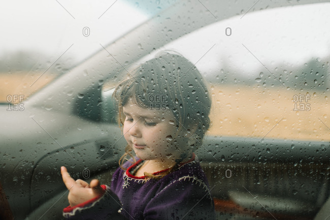 Young girl looking at moisture droplets on vehicle window