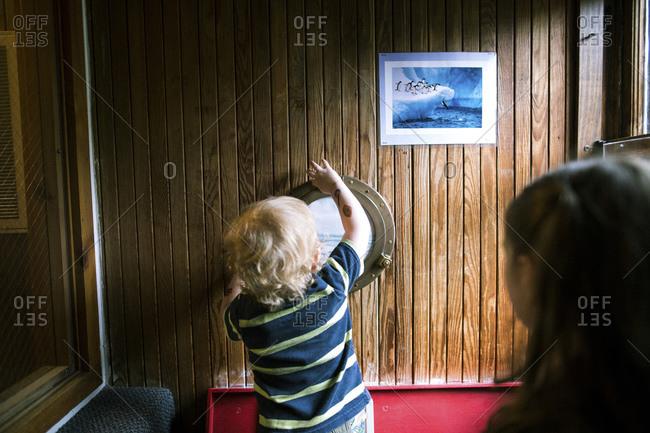 Toddler investigating a porthole