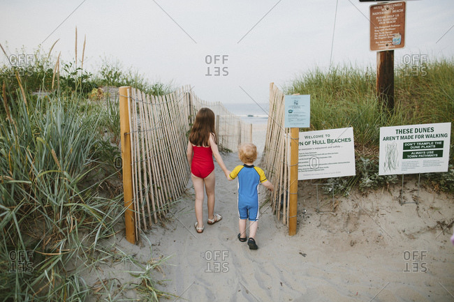 Two children holding hands, walking to the beach